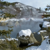 COUPLE THROUGH STEAM IN WINTER NATURAL OUTDOOR ROCK LAKE